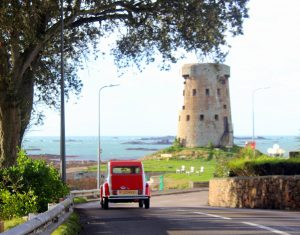 back of 2cv driving by a martello tower in St Clement, Jersey