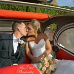 Newly wed couple kissing in 2cv