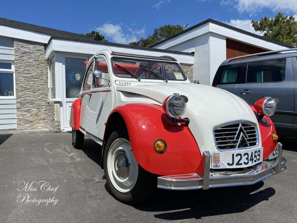 Titinne, the red and white 2 cv parked outside a bungalow.